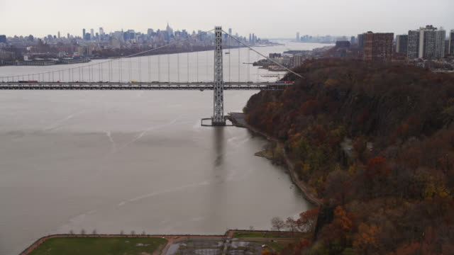 Flying along west shore of Hudson River to George Washington Bridge, New York City skyline in background. Shot in 2011.