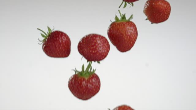 vídeos y material grabado en eventos de stock de flying and turning strawberries creating splashing droplets - frutas del bosque