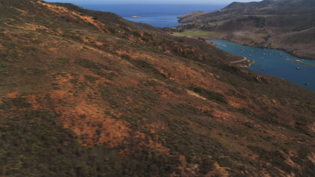 flying around a rugged hillside to a view of a harbor on santa catalina - artbeats stock videos & royalty-free footage