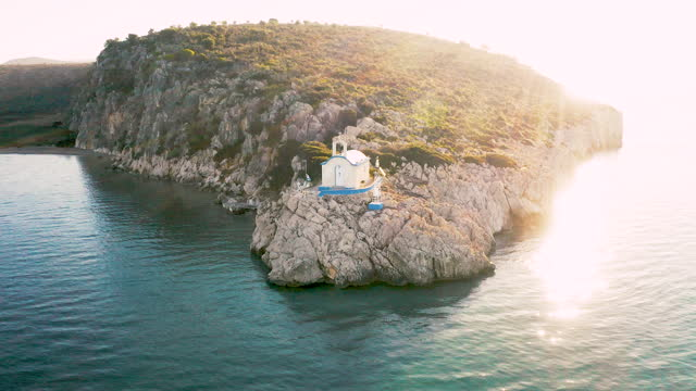 stockvideo's en b-roll-footage met flying around a small greek orthodox church on the tip of an island during sunrise - zonnig