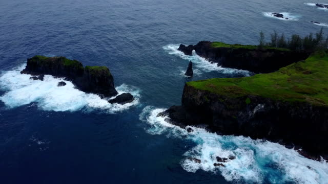 flying around edge of rocky outcrop on maui coast - solid stock videos & royalty-free footage