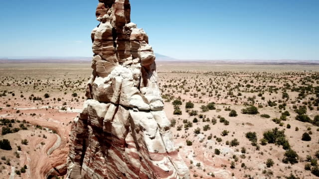 flying around giant spire in arizona desert by drone - outcrop stock videos and b-roll footage