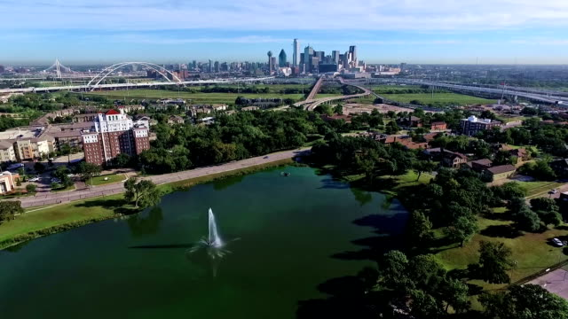 flying away from lake cliff park with fountain and pond dallas texas skyline in the distance - dallas stock videos & royalty-free footage