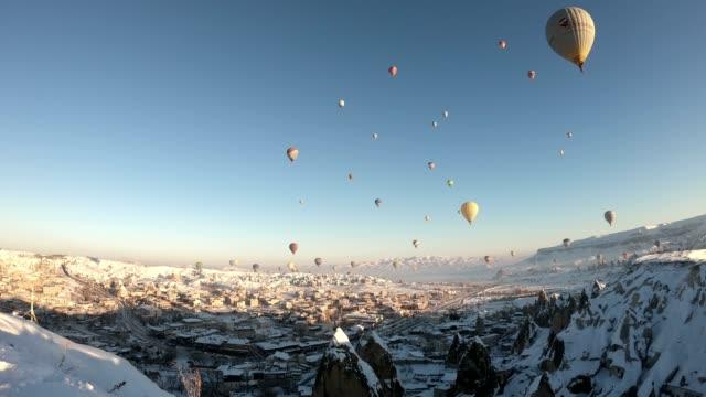 vídeos de stock, filmes e b-roll de flying balloons on a snowy day - capadócia