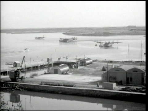 vídeos de stock e filmes b-roll de flying boats docked in water beyond dock people walking up ramp w/ lifepreserver labeled shannon airport ws workers unloading cargo from aircraft ws... - 1944