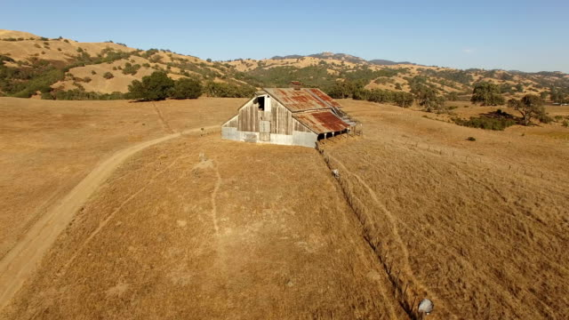 flying by old rusted barn in california - barn stock videos & royalty-free footage