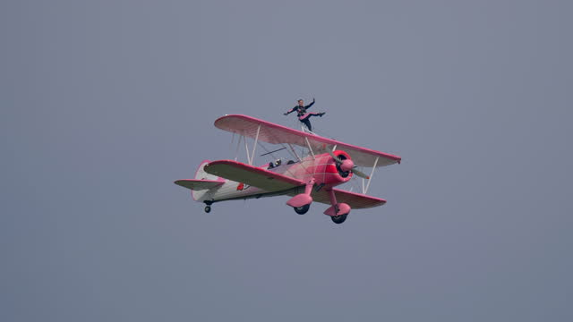 flying circus, a woman performs acrobatics on the wings of a biplane during an exhibition at the linate airshow on october 12, 2019 in milan, italy. - アドレナリン点の映像素材/bロール