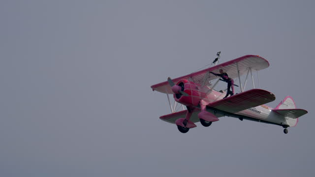 flying circus, a woman performs acrobatics on the wings of a biplane during an exhibition at the linate airshow on october 12, 2019 in milan, italy. - circus stock videos & royalty-free footage