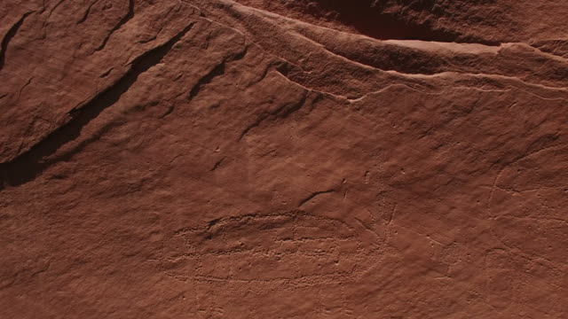 flying close to ancient carving 4k, Drone aerial view of Ancient petroglyphs anthropomorphic native american and paleolithic petroglyphs. Including horses, jesus, crosses, staff, alien and human carvings.