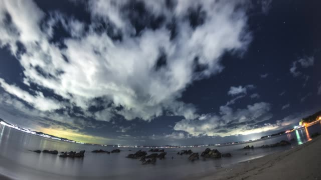 Flying cloud in a starry sky at a rocky beach of Pacific Ocean
