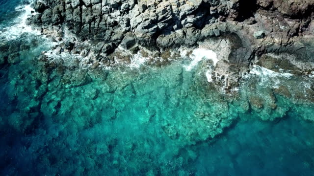 flying directly above rocky shoreline on maui island - gliding stock videos and b-roll footage