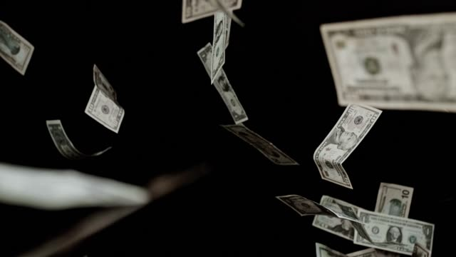 slo mo flying dollar bills on black background - excess stock videos & royalty-free footage