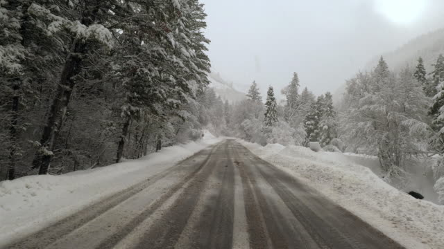 Flying down icy road during snowstorm through canyon