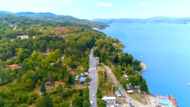vídeos y material grabado en eventos de stock de tiro de drone volando de un camino increíblemente hermoso paisaje rural y un lago cerca de él - perspectiva desde un helicóptero