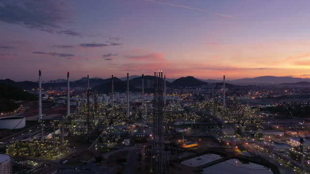 flying forward of oil and gas industry petroleum refinery in sunset time - refinery stock videos & royalty-free footage