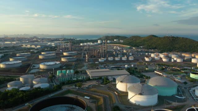 vídeos de stock, filmes e b-roll de voando para a frente do tanque de óleo na planta da refinaria no dia - refinaria