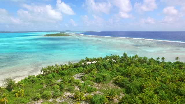 flying forward over island and lagoon towards reef and pacific ocean - aitutaki lagoon stock videos & royalty-free footage