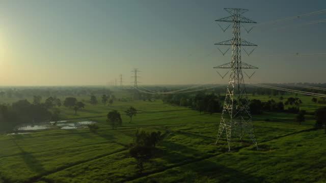 stockvideo's en b-roll-footage met vooruit vliegen naar de elektriciteitsmasten in de zonsopgang - stroomtransformator