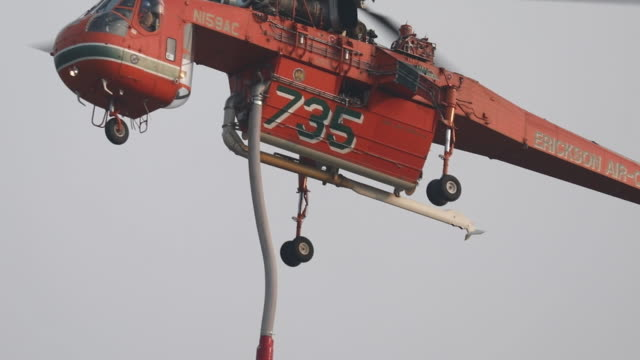flying helicopter with fire hose hanging down. bobcat fire in angeles national forest. the u.s. west is bracing for another blast of dry and windy... - sierra madre stock-videos und b-roll-filmmaterial