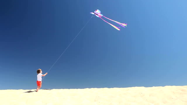 flying high – young boy flying colourful kite solo for first time - kid with kite stock videos & royalty-free footage