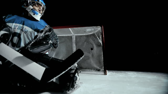 SLO MO DS Flying ice hockey puck passing the goalkeeper