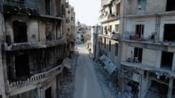 Flying in a street of Aleppo with a drone. Ravaged buildings without any windows, and burned houses.