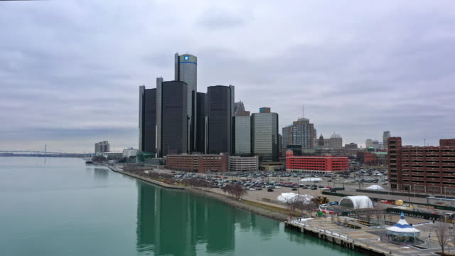 flying in towards downtown detroit from over the river - detroit river stock-videos und b-roll-filmmaterial