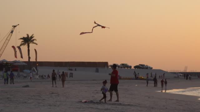 flying kites at sunset at jbr beach - dubai - 中東点の映像素材/bロール