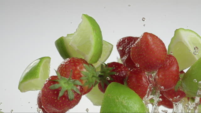 flying limes strawberries creating splashing droplets - berry fruit stock videos & royalty-free footage