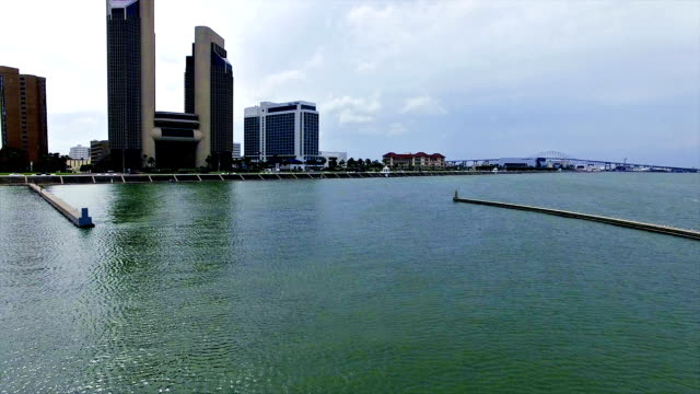 flying low over water towards corpus christi texas downtown skyline - corpus christi texas stock videos & royalty-free footage