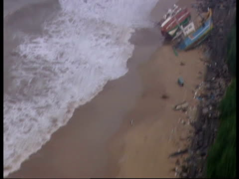 stockvideo's en b-roll-footage met flying over a beach lined with fishing boats displaced by the 2004 indian ocean tsunami. - 2004