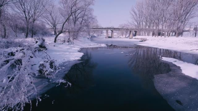 vídeos de stock, filmes e b-roll de voando sobre um rio congelado a - snow cornice