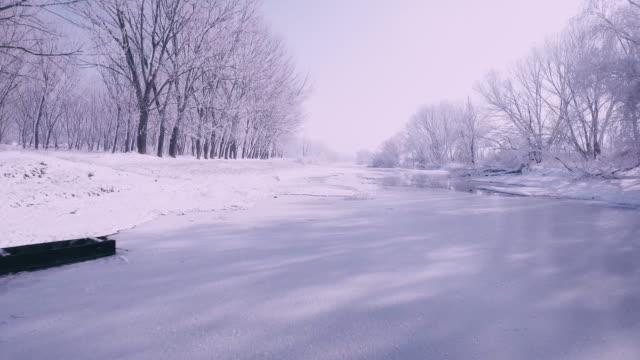 vídeos de stock, filmes e b-roll de voando sobre um rio congelado c - snow cornice