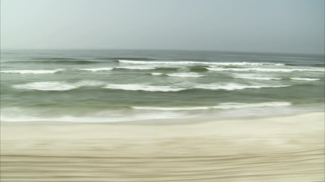 vídeos y material grabado en eventos de stock de flying over a sand beach. - omán
