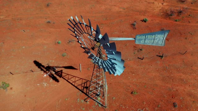 flying over a traditional windmill on a farm with dry red dirt field, australia, aerial view - weather stock videos & royalty-free footage