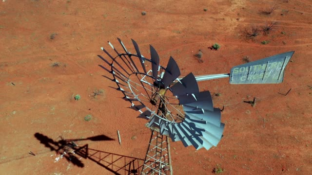 flying over a traditional windmill on a farm with dry red dirt field, australia, aerial view - turbine stock videos & royalty-free footage