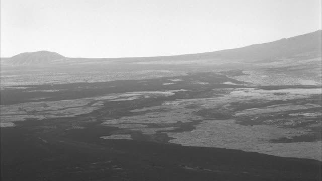 ws arial flying over barren hilly lava country at kona hawaii - pacific ocean stock videos & royalty-free footage
