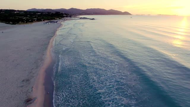 luftaufnahme: fliegen über strand bei sonnenaufgang - sardinien stock-videos und b-roll-filmmaterial