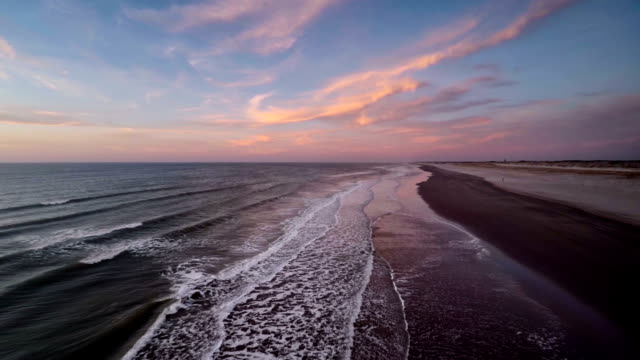 stockvideo's en b-roll-footage met flying over beach at sunset - schemering