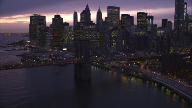 Flying over Brooklyn Bridge at dusk toward skyscrapers of Financial District in Lower Manhattan. Shot in 2011.