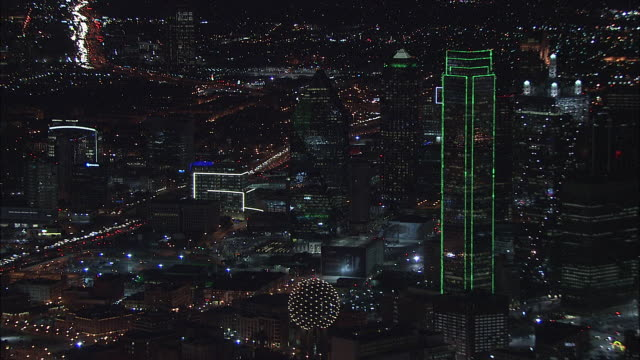 Flying over busy highway interchanges illuminated w/car headlights city lights buildings of downtown Dallas skyline including Reunion Observation...