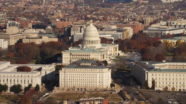 vídeos de stock, filmes e b-roll de flying over capitol hill from south capitol street to pennsylvania avenue with rayburn house office building in front of capitol. shot in 2011. - senado governo