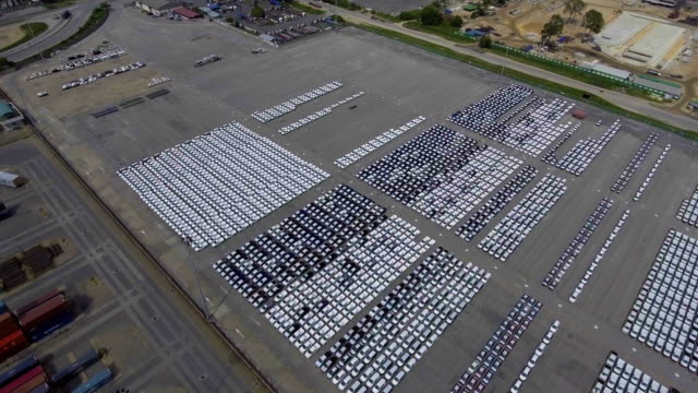 Flying over Car import parking lot, car line up, containers, ship, industrial port