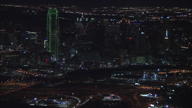 Flying over city lights of downtown Dallas busy highway interchanges toward highrise buildings skyscrapers of skyline JP Morgan Chase Tower...