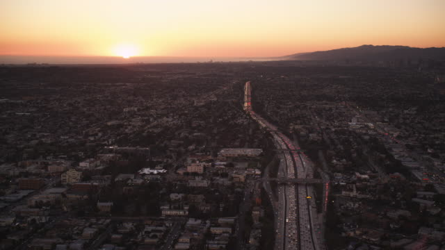 Flying over cityscape and freeways of Los Angeles with sunset in distance. Shot in October 2010.
