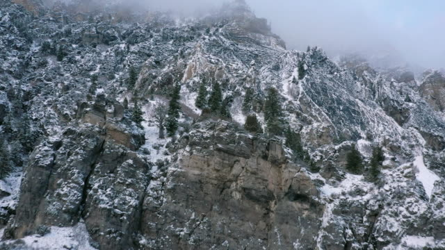 flying over cliffs covered in snow viewing the rocky terrain - american fork city stock videos & royalty-free footage