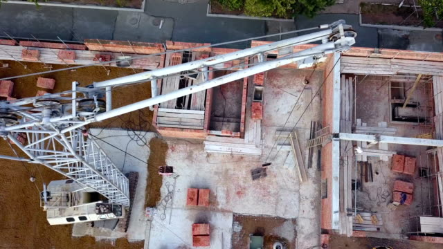 flying over construction site with crane on it - brick stock videos & royalty-free footage