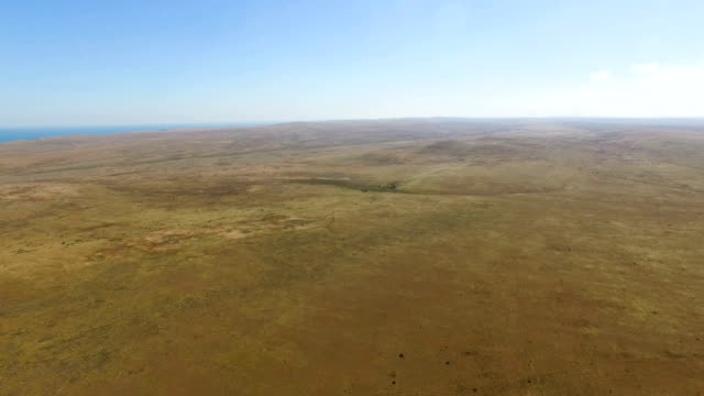 AERIAL: Flying over deserted hilly plains towards blue sea