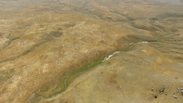 AERIAL: Flying over deserted hilly plains