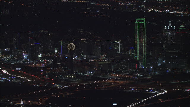 Flying over downtown Dallas city lights busy highways interchanges Reunion observation Tower Bank of America Plaza Renaissance Tower highrise office...